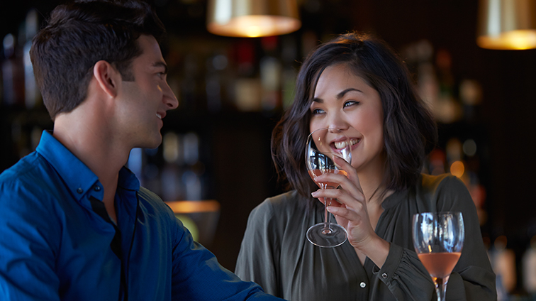 A lady and man enjoying a glass of wine